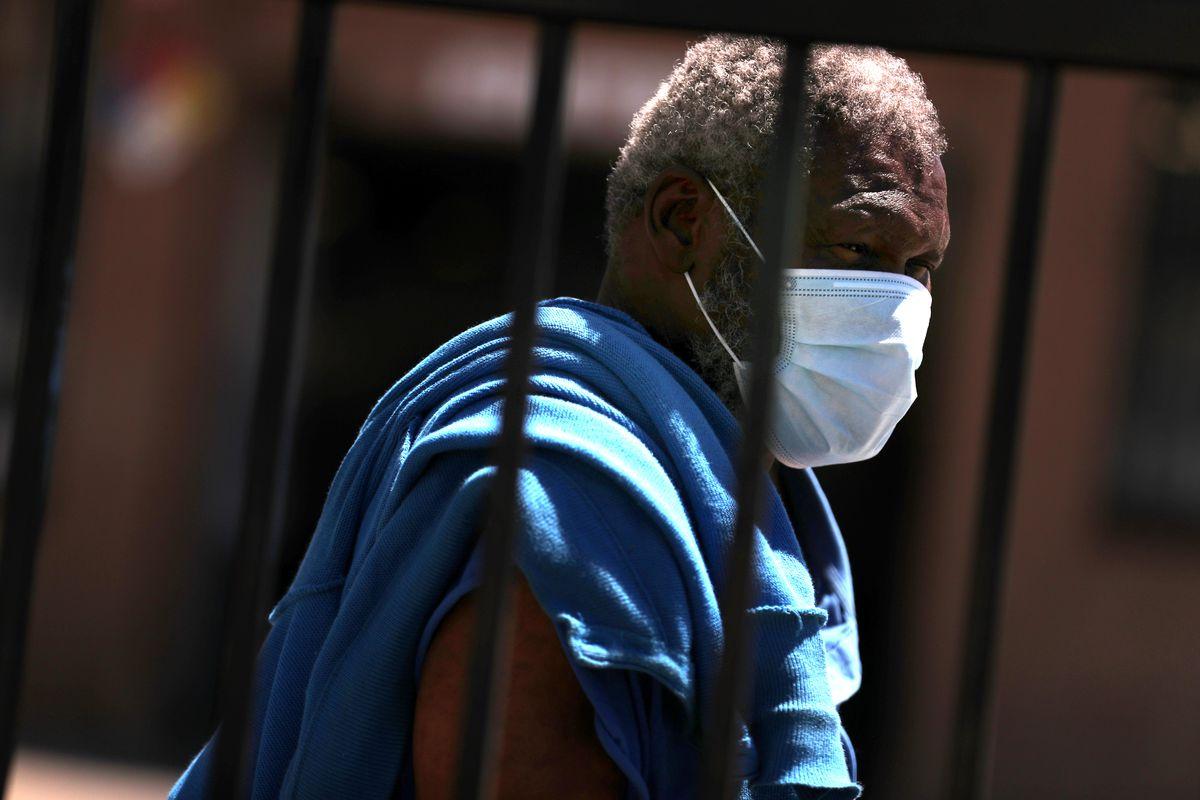An African American man wears a face mask.