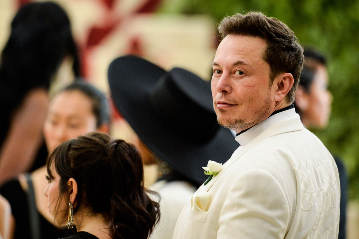 Elon Musk gazes into the camera at a charity gala.