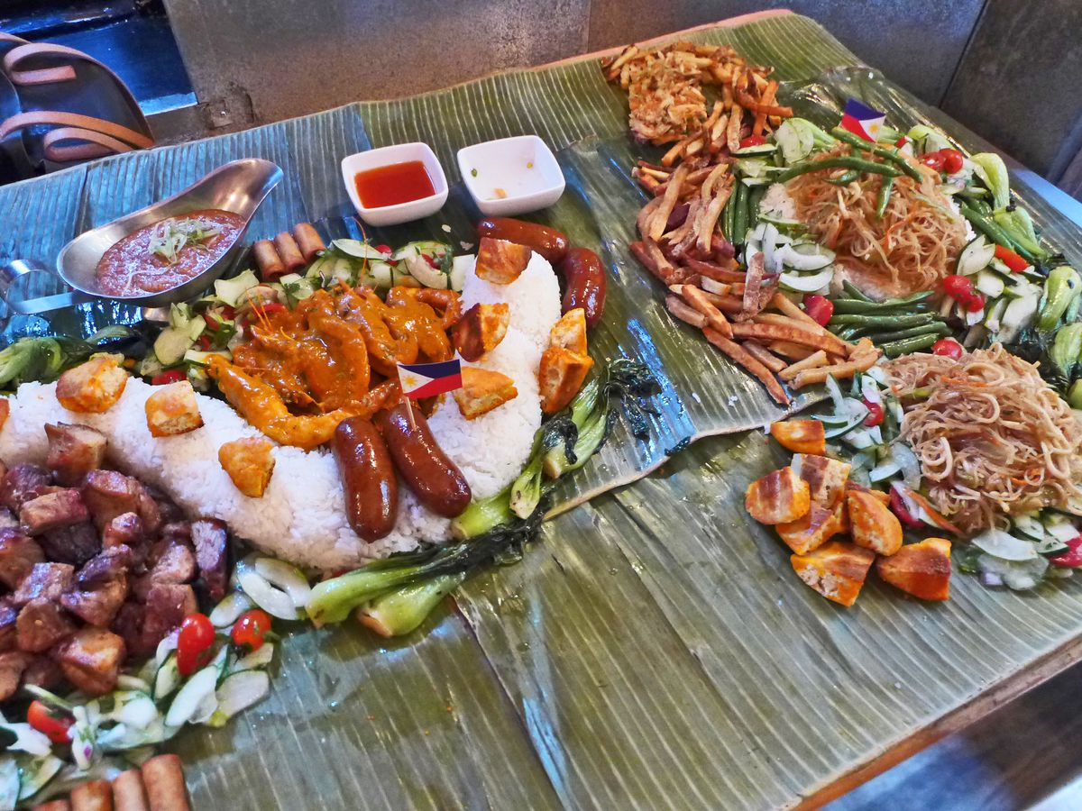 A gorgeous buffet including shrimp, sausages, rice and other dishes on a grooved green table.