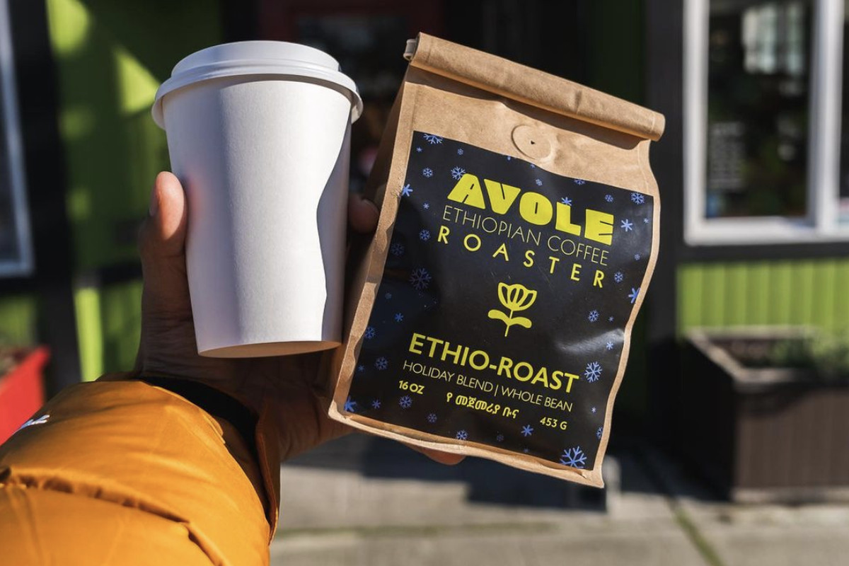 """A person holds up a paper coffee cup next to a bag that says """"Avole Ethiopian Coffee Roaster"""""""