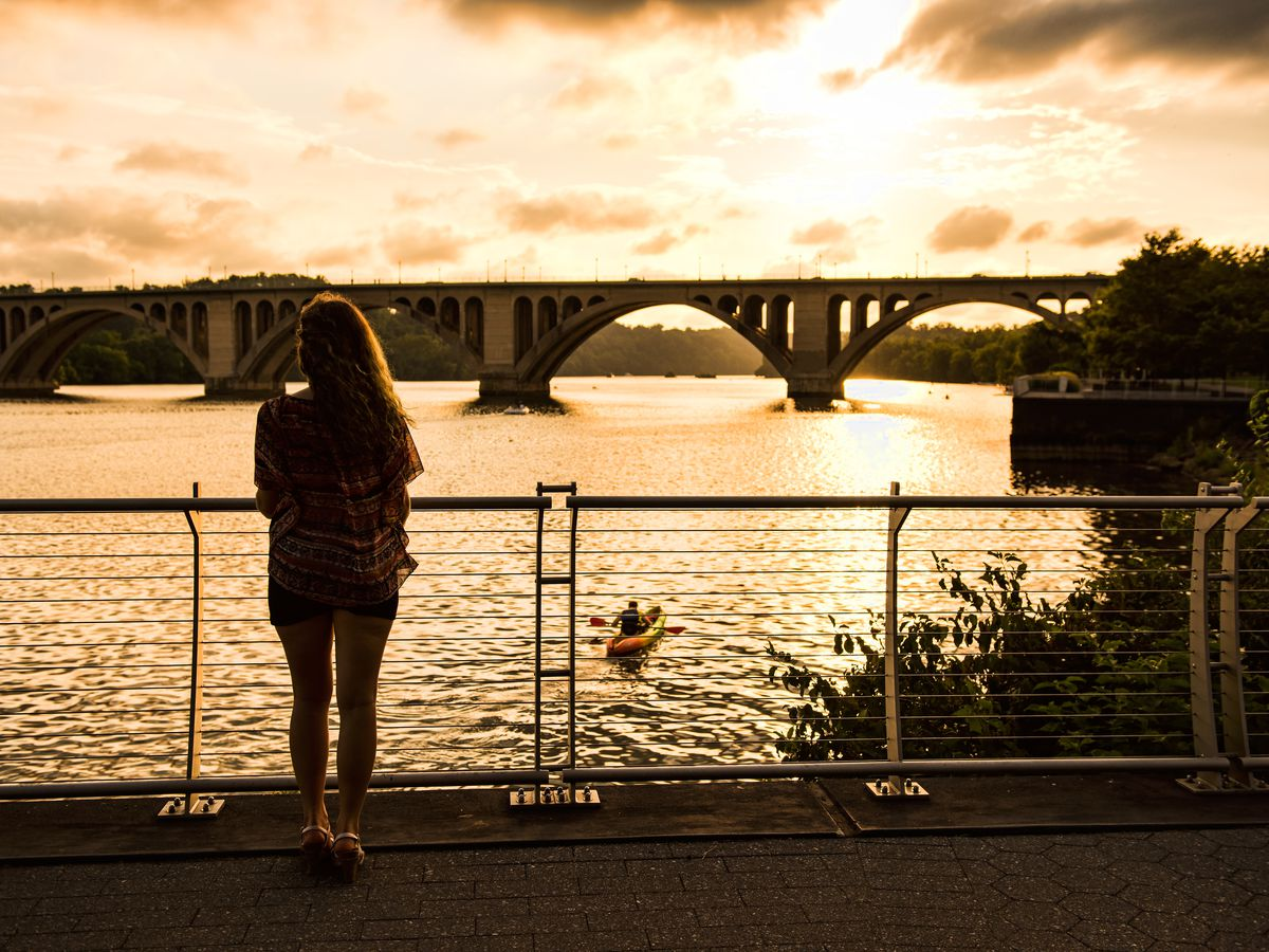 A young woman looks at out a river, where a person is kayaking. There is a large, arched bridge in the background.