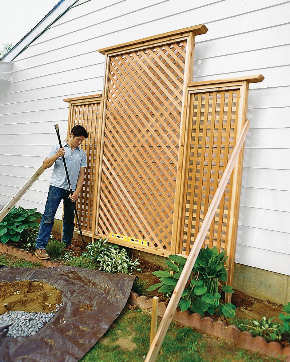 Man Installs Trellis Against Wall Of House