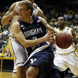 BYU guard Tyler Haws, foreground, dribbles past Southern Mississippi forward Jonathan Mills in the second half of their NIT college basketball game in Hattiesburg, Miss., Wednesday, March 27, 2013.