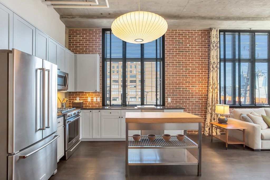 A brick kitchen with white cabinetry and a small island.