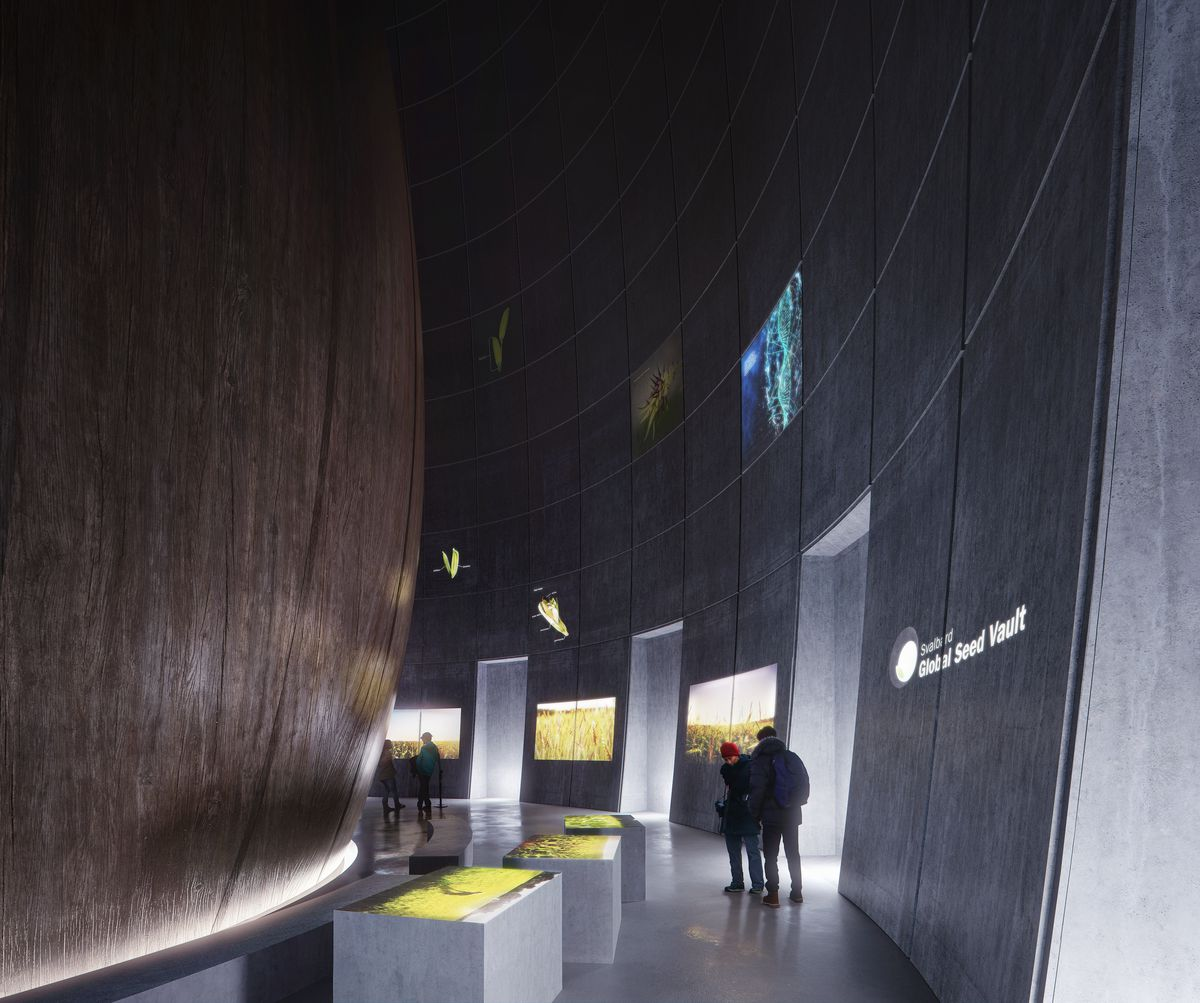 People milling around a dark exhibition space with digital projections on the wall.