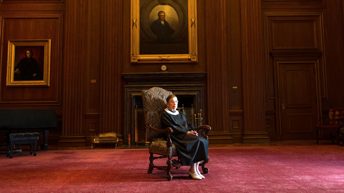 Supreme Court Justice Ruth Bader Ginsburg sitting in a high-backed chair in front of a fireplace and below a large portrait.