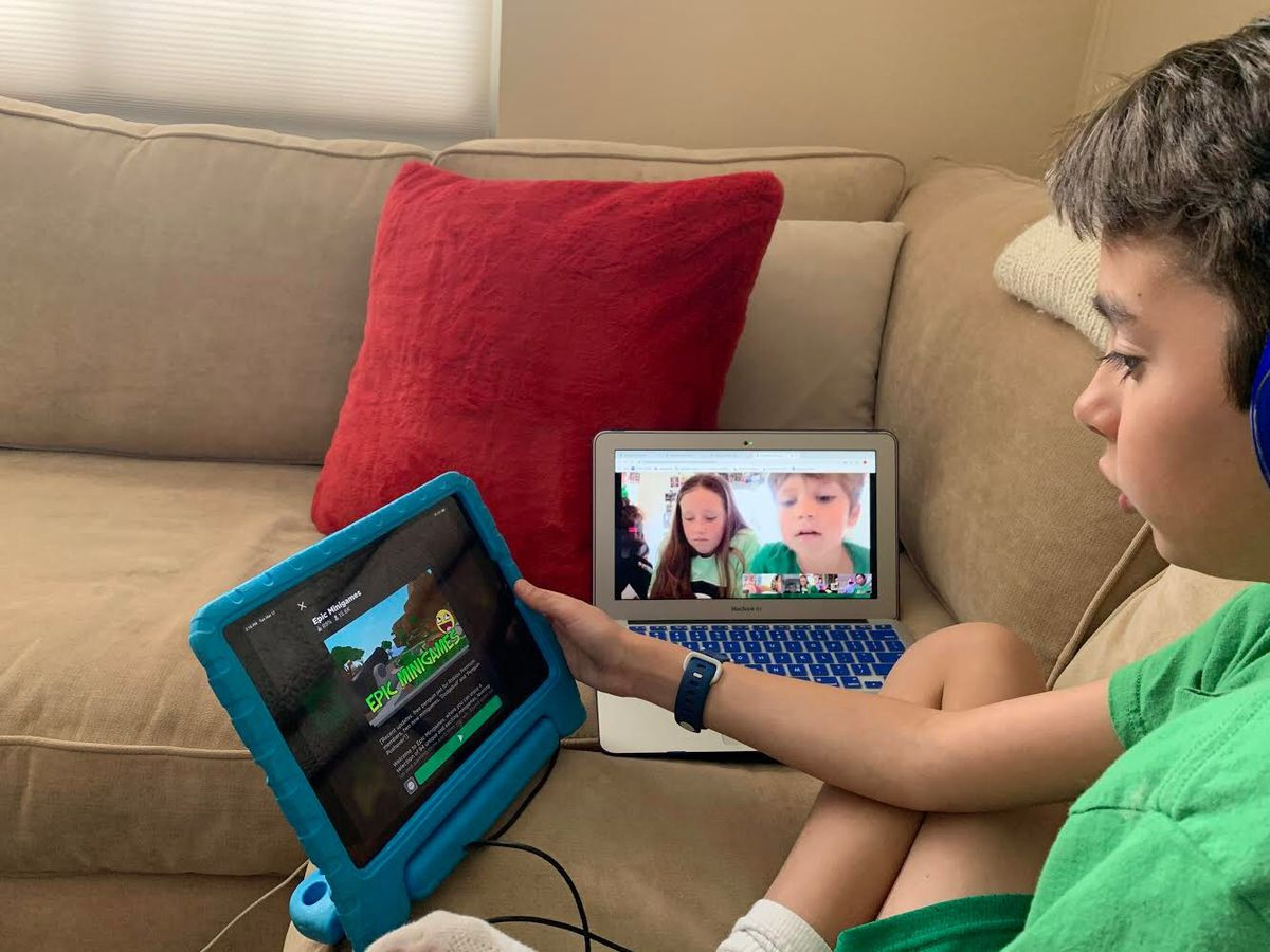A child plays Roblox on his tablet; next to him, a laptop shows the camera of his two friends.