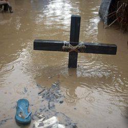 A voodoo cross in honor of the Baron Samedi stands in floodwaters, triggered by Tropical Storm Isaac, at a place of worship in Port-au-Prince, Haiti, Saturday, Aug. 25, 2012. Tropical Storm Isaac swept across Haiti's southern peninsula early Saturday, dousing a capital city prone to flooding and adding to the misery of a poor nation still trying to recover from the 2010 earthquake.