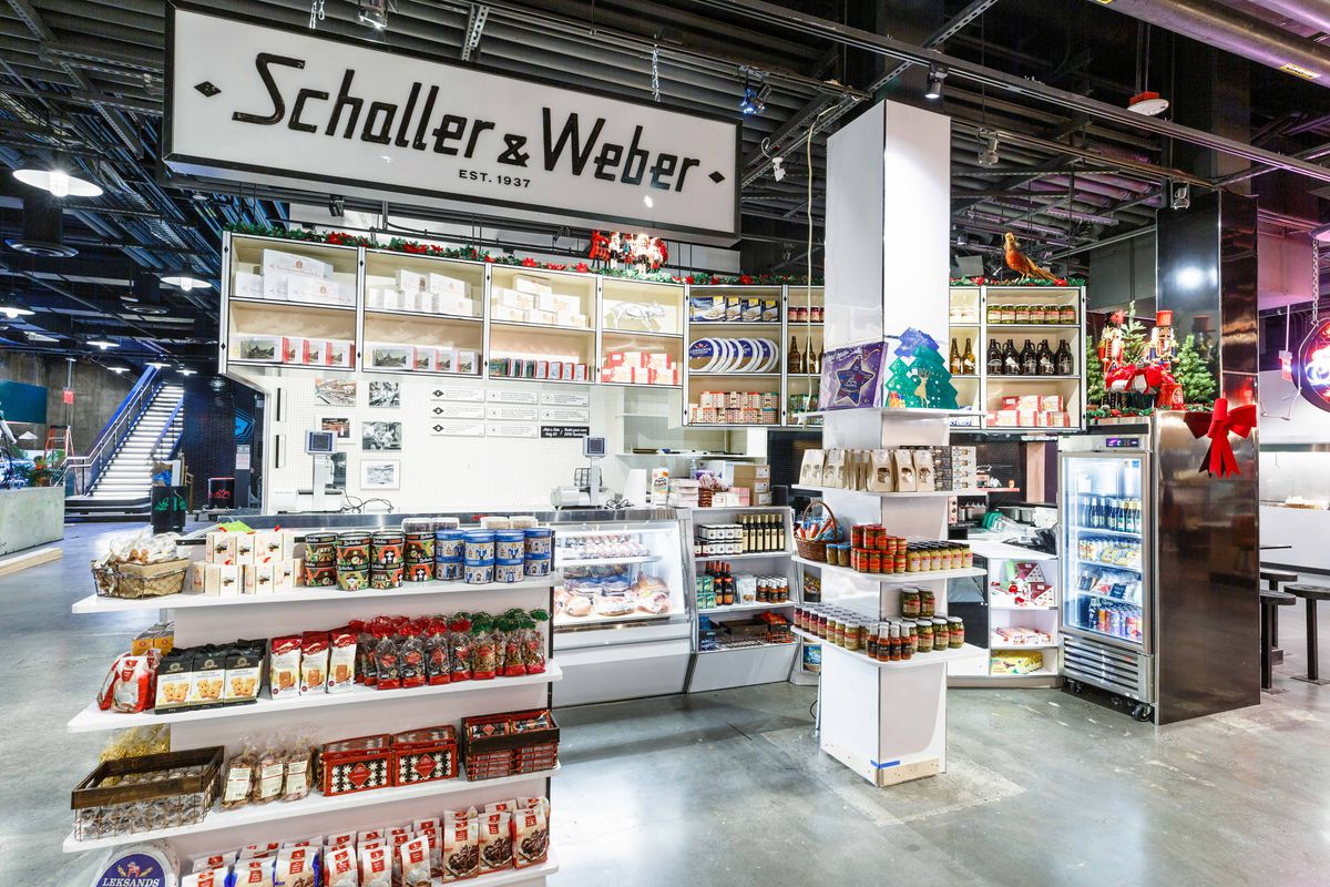 A white sign saying Schaller & Weber hangs above shelves stocked with grocery goods.