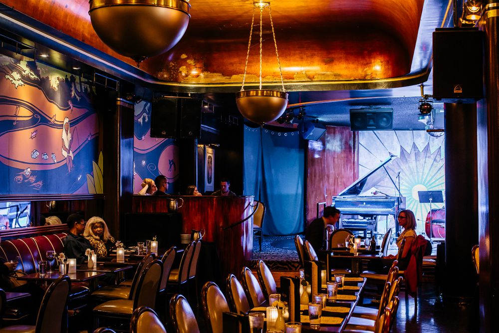 A blue and gold light is cast across deco murals and silver light fixtures at Cliff Bell's.