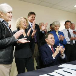 """FILE: Gov. Gary R. Herbert, center, is joined by homeless advocate Gail Miller, left, Salt Lake City Mayor Jackie Biskupski, Utah House Majority Leader Jim Dunnigan, R-Taylorsville, homeless advocate Pamela Atkinson, Rep. Steve Eliason, R-Sandy, and David Patton, former director of the Utah Department of Health, as he signs two bills """""""" HB436 and HB437 """""""" at the Fourth Street Clinic in Salt Lake City on Friday, March 25, 2016. HB346 will pump $9.25 million into homeless services and shelters, the first of three years of funding that should eventually amount to $27 million. HB347 will provide $15 million to expand Medicaid coverage to the state's poorest of the poor."""
