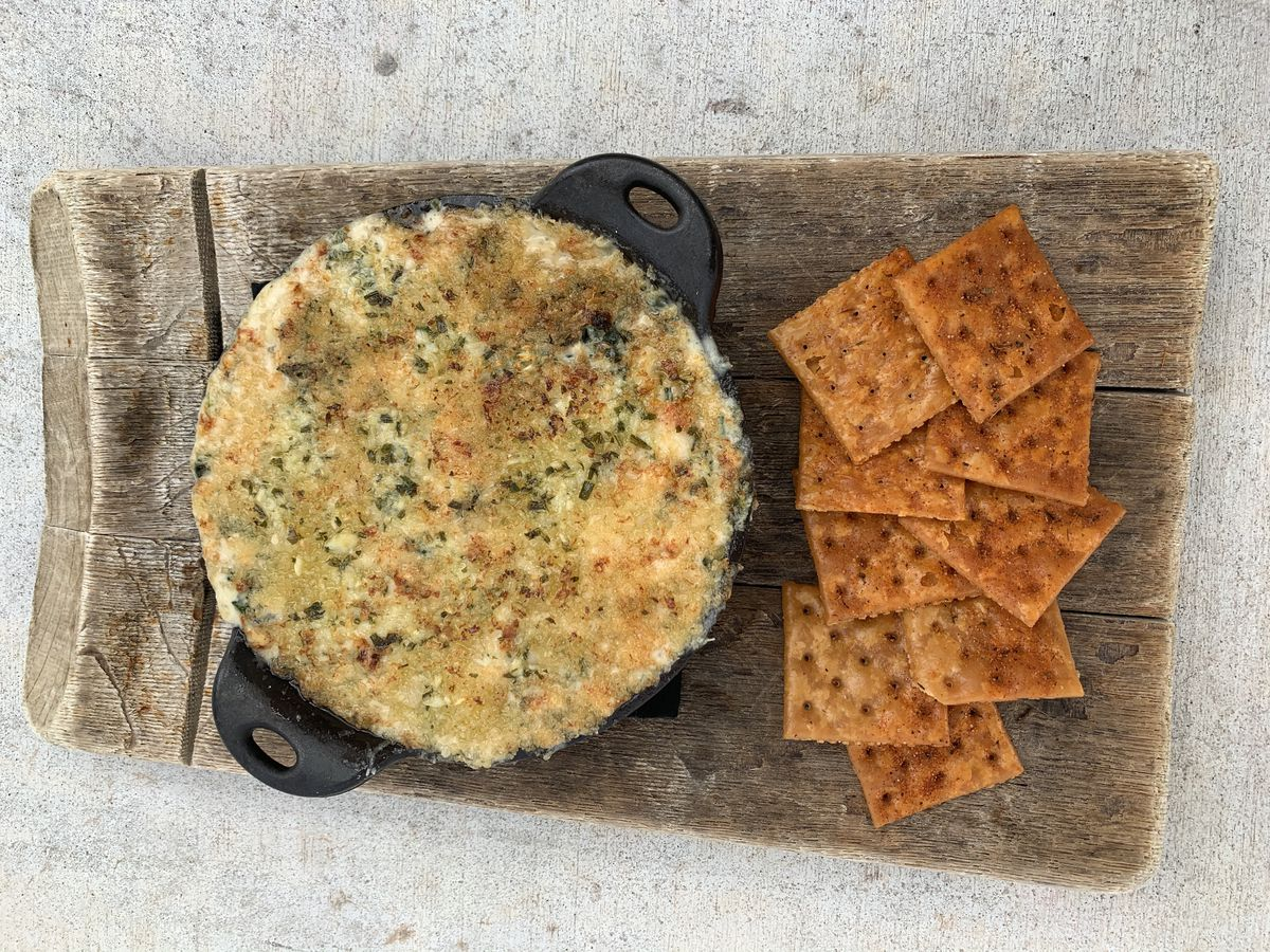 Crab dip in a cast-iron bowl served with spices crackers