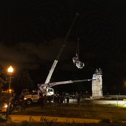 A crane removes the Christopher Columbus Statue in Grant Park from its plinth, Friday, July 24, 2020.