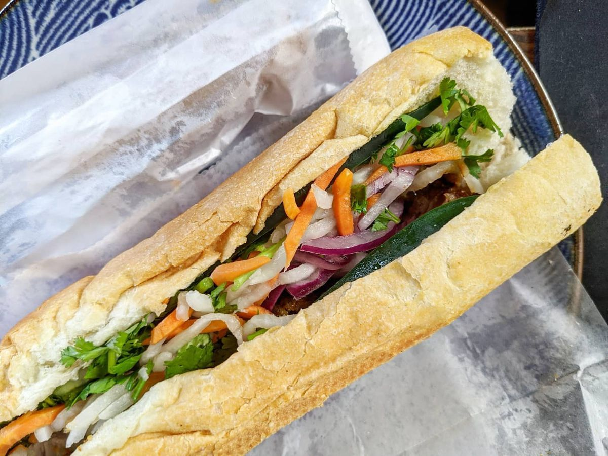 A Vietnamese baguette is packed with various pickled vegetables and grilled meats
