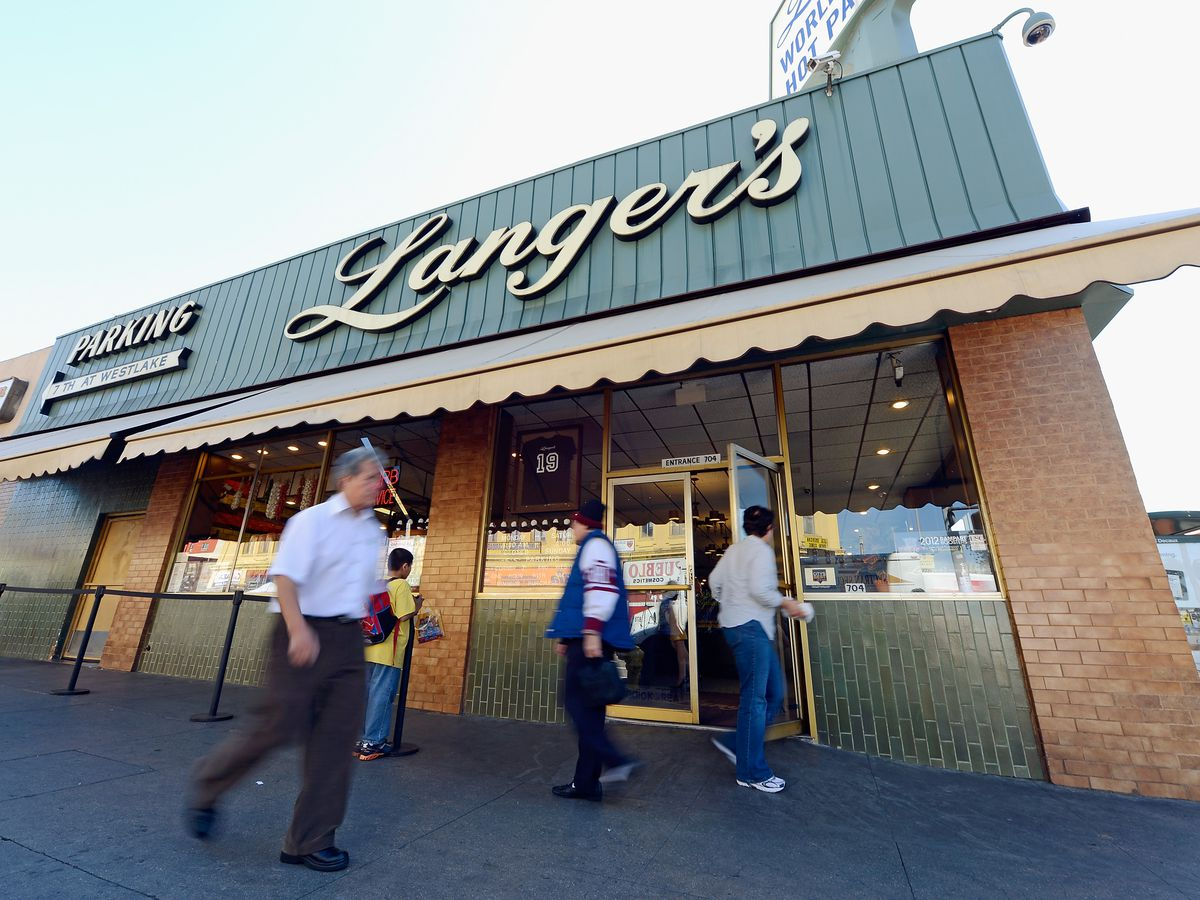 The exterior of Langer's Delicatessen in Los Angeles, California. The facade is brick with windows and a green metal sign that reads: Langer's.