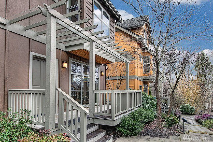 A brownish three story townhouse. The front porch is gray and has a trellis on top. The townhouse next door, in the background, is orange.
