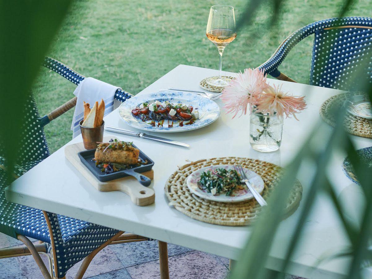 通过棕榈叶子在桌子上设置的棕榈叶与葡萄酒和盘子。