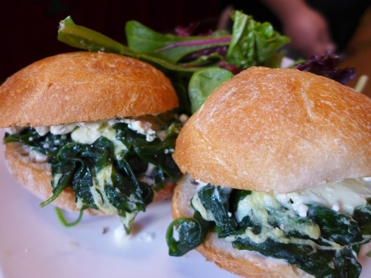 A pair or rolls with green spinach inside and white dressing lolling out.