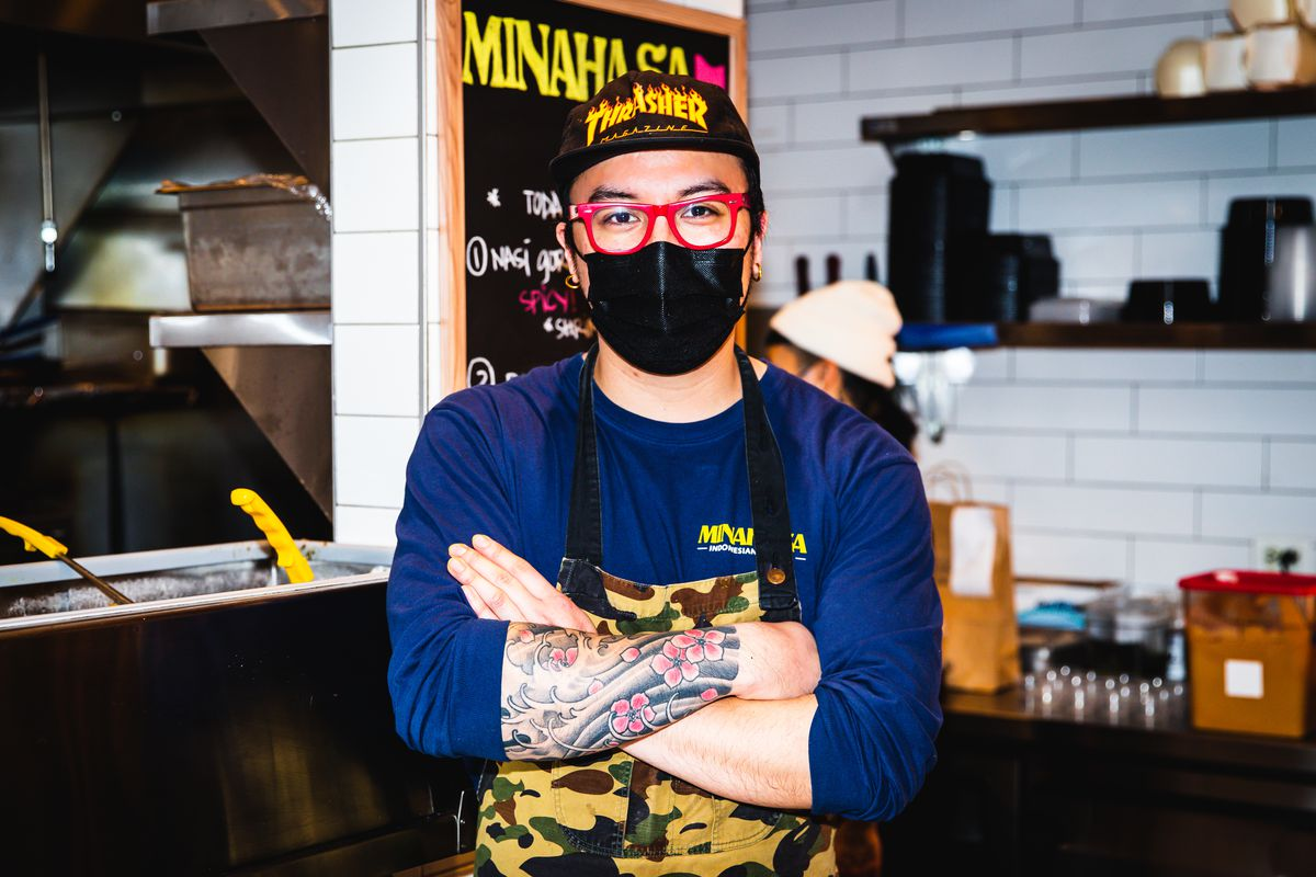 A male chef stands with his arms crossed inside a food hall kitchen.