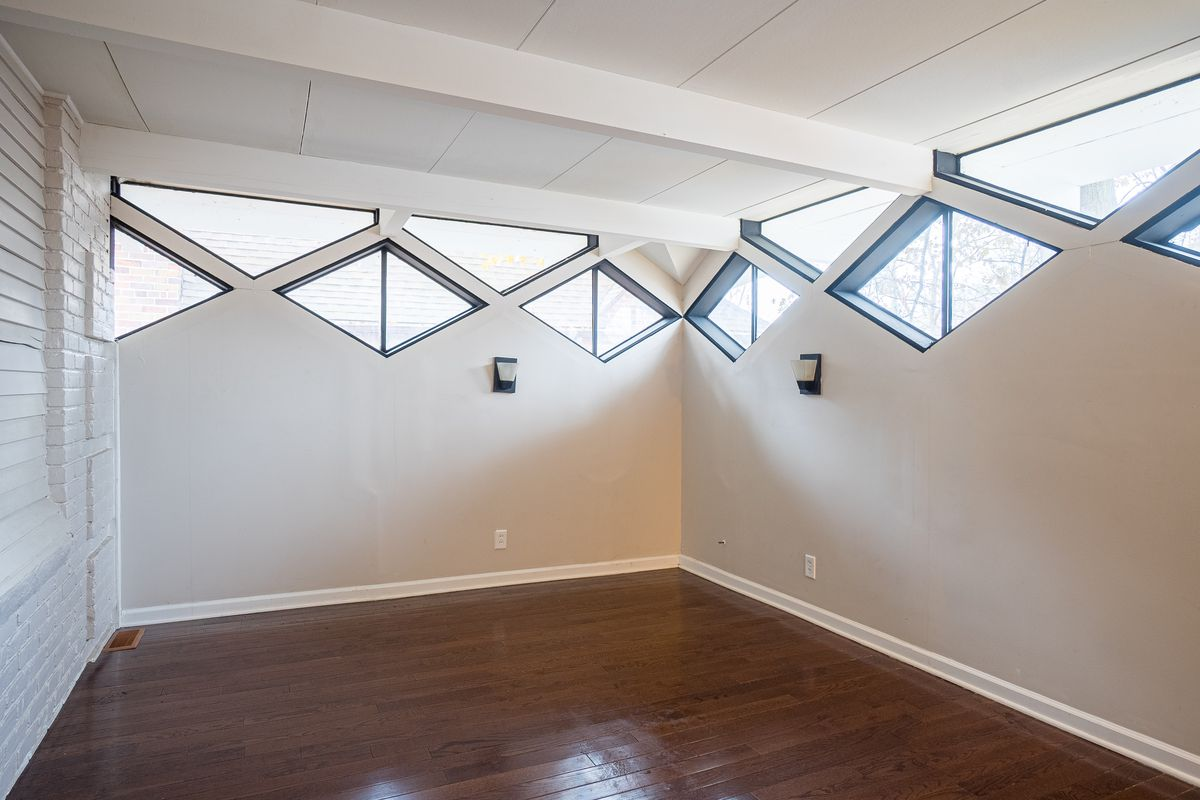 An empty room with a white brick wall on one side, and white walls with diamond windows on the other two walls.