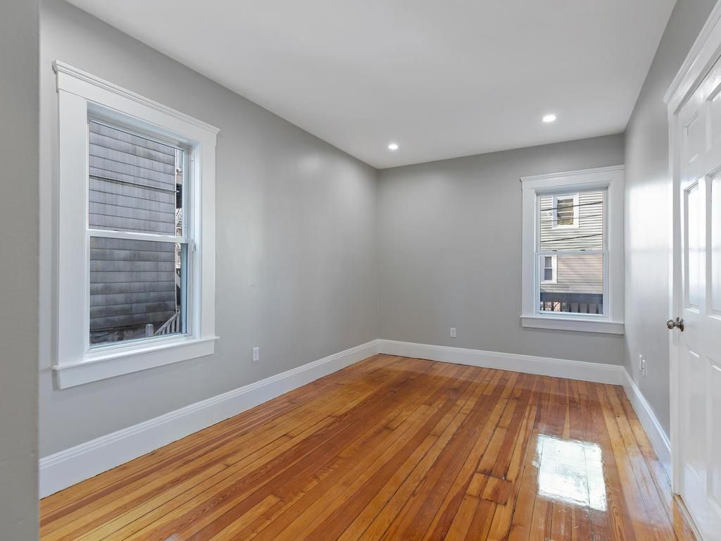 An empty bedroom with two windows.