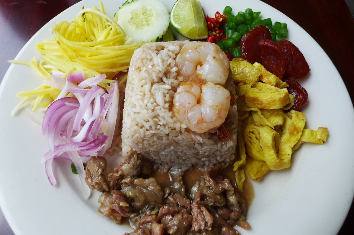 Khao kluk kapi comes on a white plate with a block of rice, shrimp, beets, egg ribbons