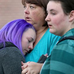 Pleasant Grove High School student Kalie Nutt is held by Camie Miller and Taryn Miller after a lockdown at the high school was lifted Thursday, Dec. 3, 2015. Pleasant Grove High School was placed on lockdown after receiving reports of a man with a weapon inside the school. Miller's daughter, Taryn, looks on.