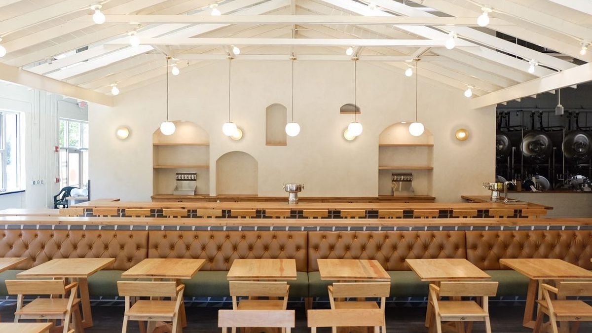 A white vaulted ceiling with exposed beams above the dining room with a row of natural colored two-top tables and chairs and an Army green and camel leather banquet; five pendant lights hang above the bar in the background