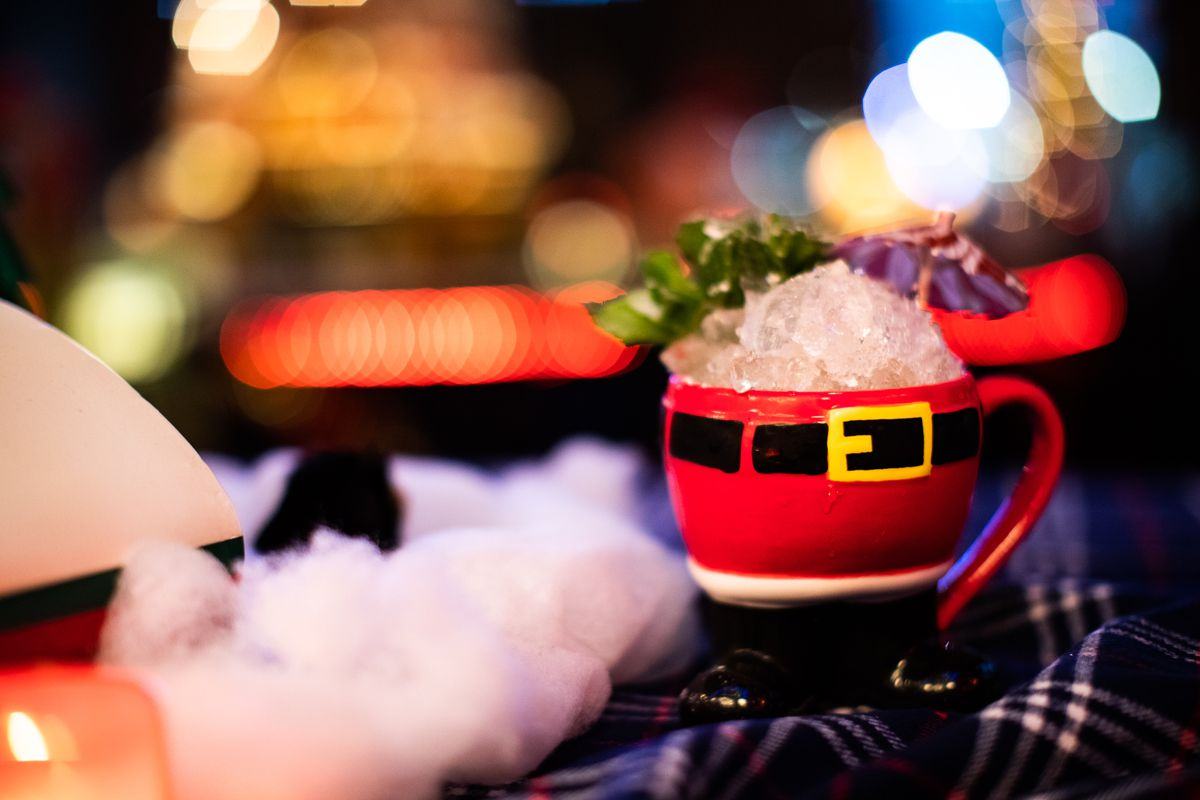 A santa mug overflowing with crushed ice and an umbrella sits on a piece of blue fabric next to white cotton fluff.