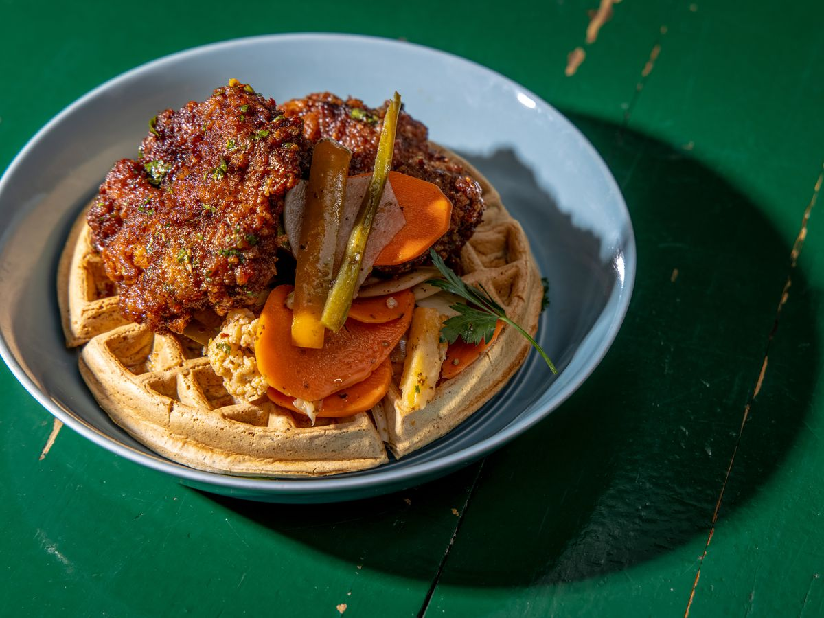 Dark brown sumac fried chicken sits over falafel waffles with pickled carrots; the plate sits above a green table