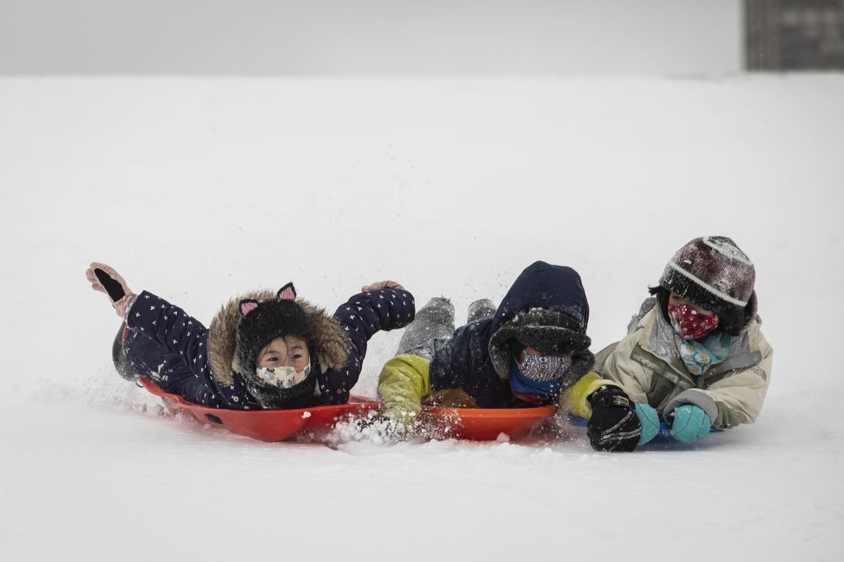 Nari Berthusen, 9, (from left) and her friends Eito, 8, and Eita Tabion, 10, sled down Cricket Hill near Montrose Beach on the North Side after several inches of snow fell overnight across Chicago, Monday afternoon, Feb. 15, 2021.