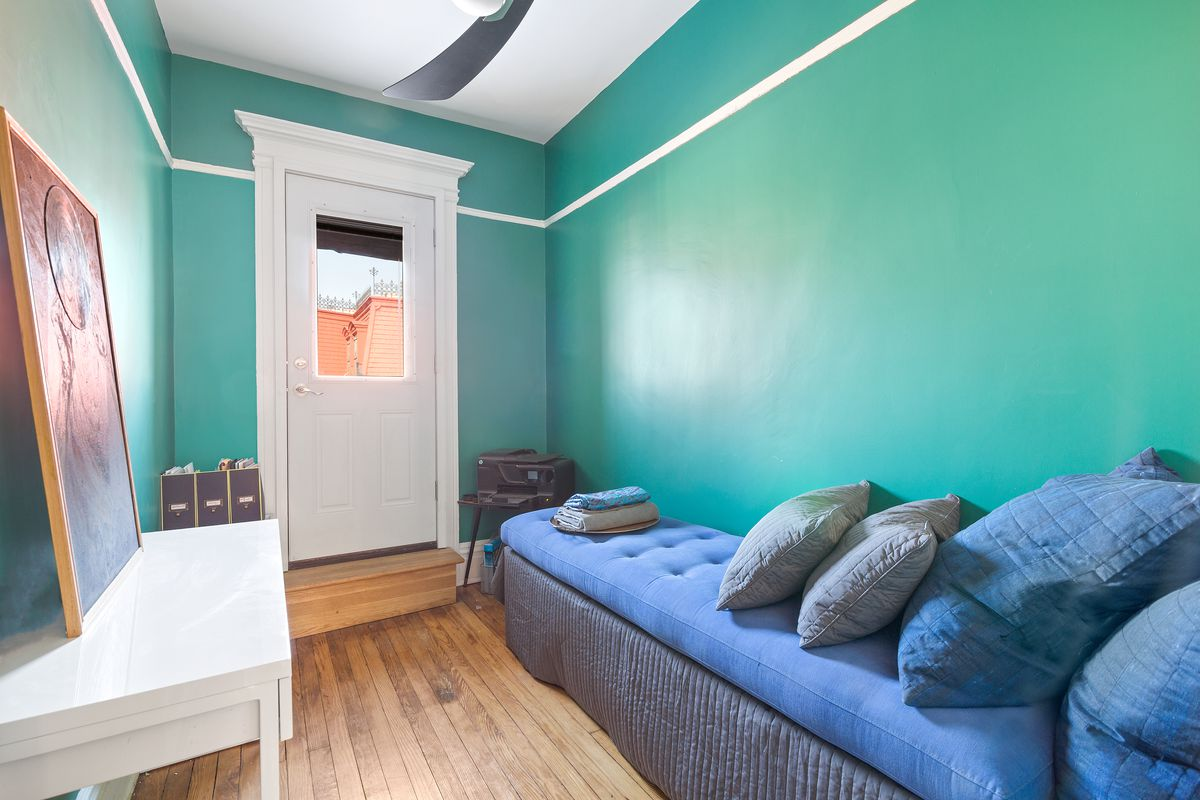 A nook with a bright blue couch, green walls, and a white table.