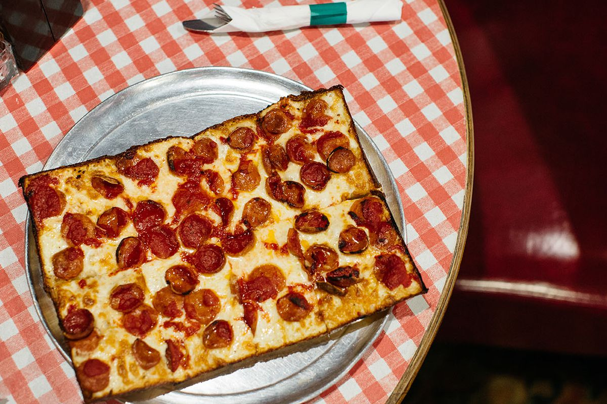 A square pizza with pepperoni on a round table with a red and white checked tablecloth.
