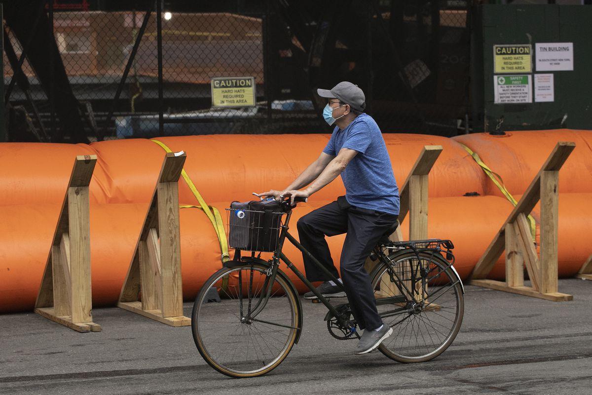A man wearing a mask on a bike rides past a highlighter-orange flood barrier.