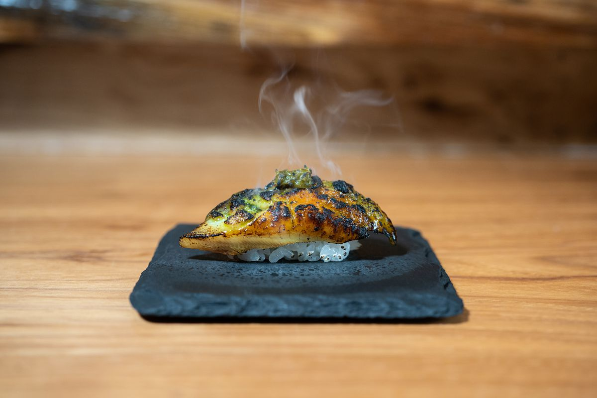 A piece of sushi consisting of charred yellowish meat with smoky wisps on top of a clump of rice on a stone plate on top of a wooden table