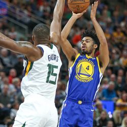 Golden State Warriors guard Quinn Cook (4) shoots over Utah Jazz forward Derrick Favors (15) during the game at Vivint Arena in Salt Lake City on Tuesday, April 10, 2018.