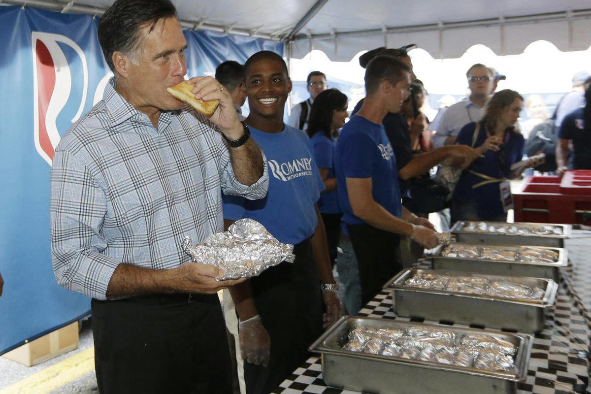 Republican presidential candidate Mitt Romney takes a bite out of a hot dog as he campaigns at the Federated Auto Parts 400 NASCAR Sprint Cup Series race at Richmond International Raceway in Richmond, Va., Saturday, Sept. 8, 2012.