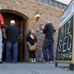 Patrons wait to go into a downtown bar as a sign refers to Missouri's entrance into the Southeastern Conference before an NCAA college football game between Georgia and Missouri Saturday, Sept. 8, 2012, in Columbia, Mo. The football game will be the first for Missouri against a Southeastern Conference opponent since joining the conference.