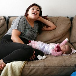 Adriana Carreon sits with her baby Adriana at home in Taylorsville on Saturday, Feb. 9, 2013. Carreron's family was recently evicted, but they managed to land on their feet.