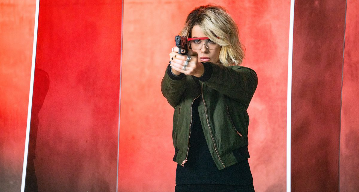 Kate Beckinsale fires a pistol in front of a vivid orange and red background in Jolt