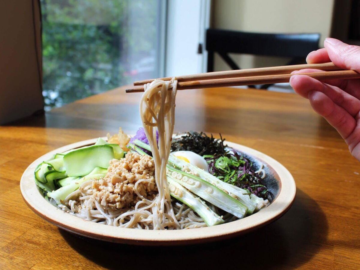 Chopsticks pulling buckwheat soba from a plate of green vegetables.