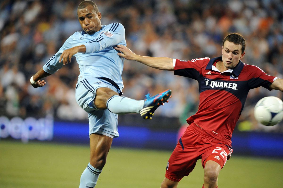 Jun 29, 2012; Kansas City, KS, USA; Chicago Fire defender Austin Berry (22) defends against Sporting KC  forward Teal Bunbury (9) in the second half at Livestrong Sporting Park. Chicago won the game 1-0. Mandatory Credit: John Rieger-US PRESSWIRE