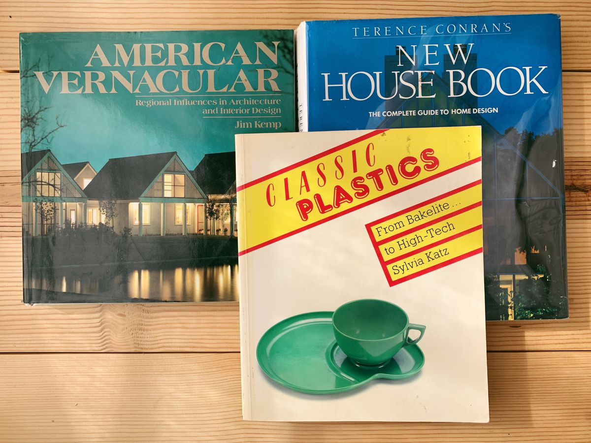 Three vintage books sit on top of a wooden surface. One book has a few white houses on its cover, another has a green mug on top of a plate.