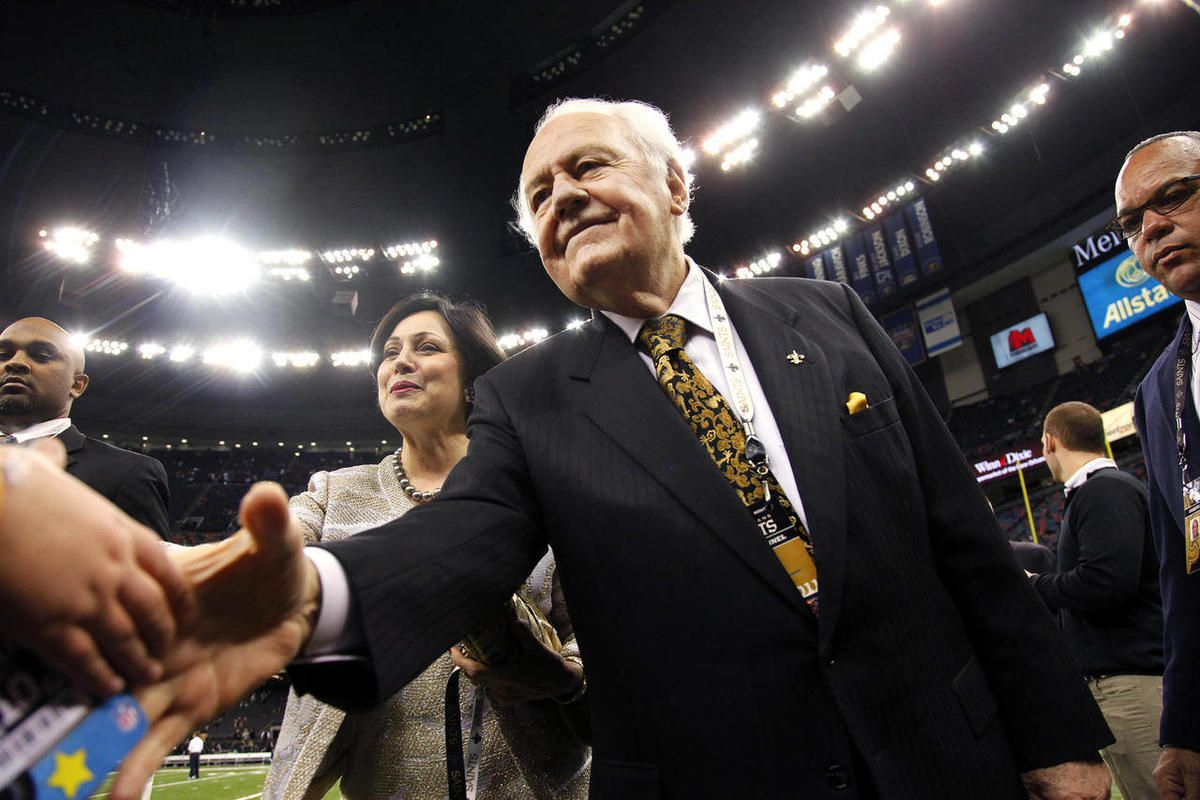 FILE - This Jan. 1, 2012 file photo shows New Orleans Saints owner Tom Benson and his wife Gayle Benson shaking hands before an NFL football game against the Carolina Panthers in New Orleans. A person familiar with the deal says the NBA has agreed to sell