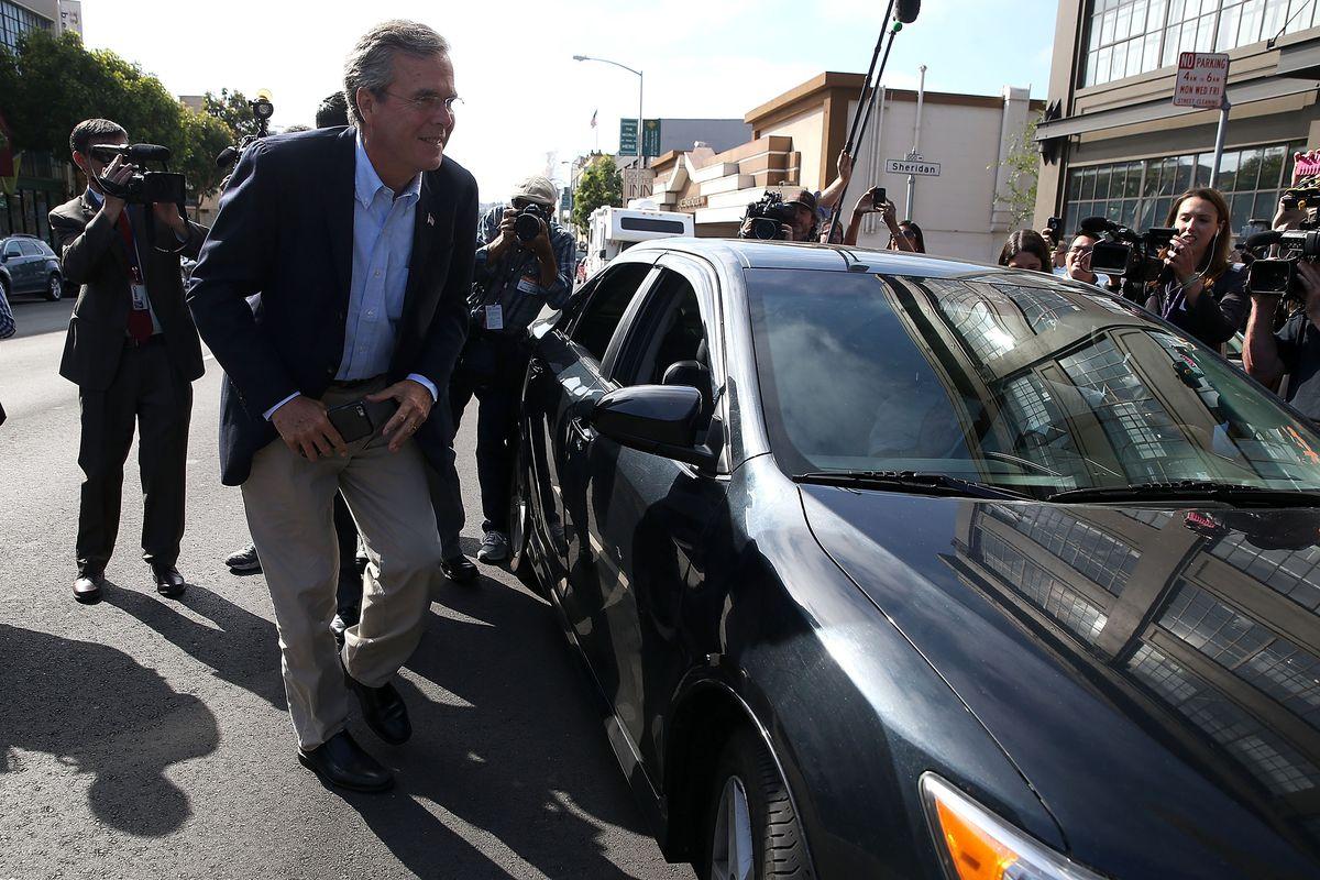 Jeb Bush exits his Uber vehicle at a San Francisco campaign stop.