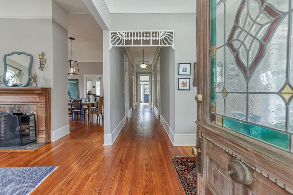 A central hallway with rooms branching off in an old house.