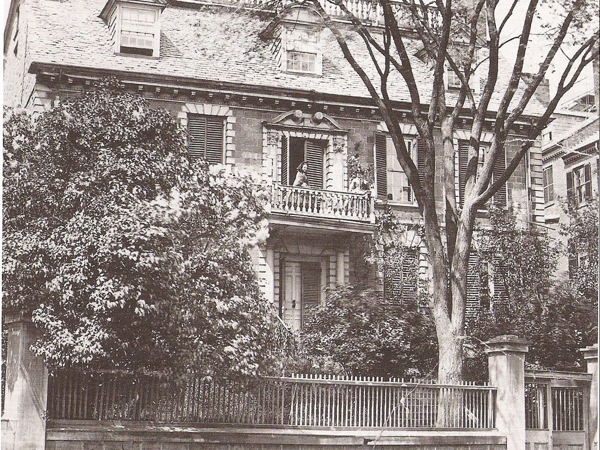 An old photograph of a three-story house behind trees.