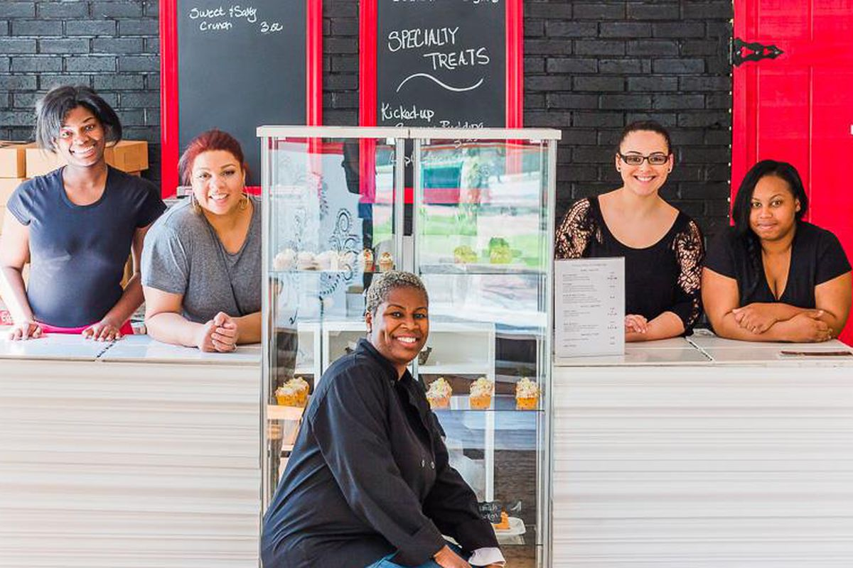 Owner Mona Wilson (center) and team pose in the bright, mural-strewn new shop.