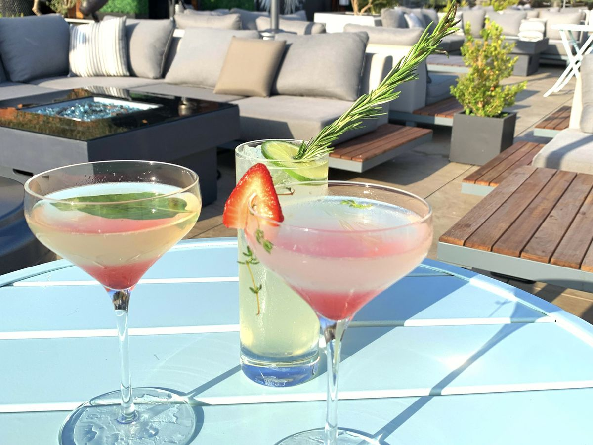 Three cocktails in a coupe and tumbler glasses sit on a pale blue outdoor table