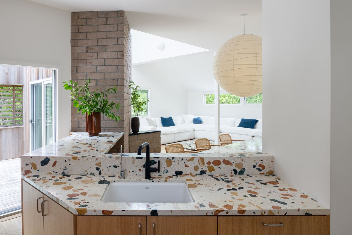A L-shaped kitchen island features terrazzo-style counters, white sink, black faucet, and a view in the living area with a large white couch.